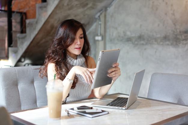 Schöne asiatische frau im freizeitkleidereinkaufen und in der online-zahlung auf tablette und computer
