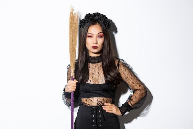 Schöne asiatische frau im gotischen spitzenkleid und im schwarzen kranz, der besen hält und misstrauisch in die kamera schaut, über weißem hintergrund stehend.
