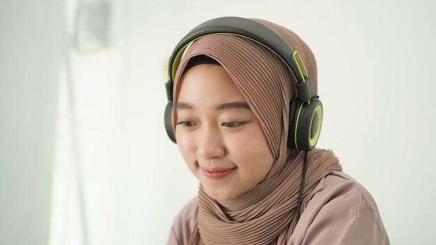 Schöne asiatische frau im hijab hört aufmerksam zu
