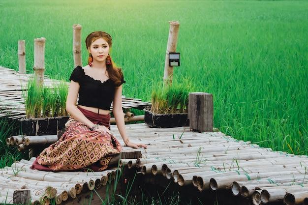 Schöne asiatische frau im lokalen kleid, das auf bambusbrücke im reisfeld natürlich sitzt und genießen