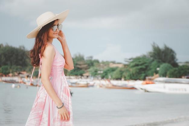 Schöne asiatische frau im rosa kleid an einem tropischen strand porträt einer glücklichen jungen frau lächelnd