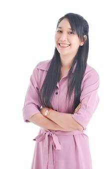 Schöne asiatische frau im rosa kleid, das gekreuzten arm tut und über weißem raum lächelt.