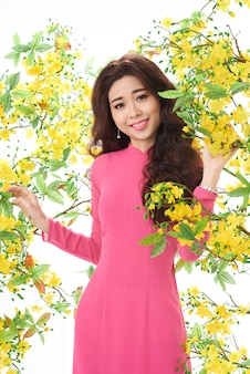 Schöne asiatische frau im rosafarbenen kleid, das im blühenden busch steht
