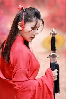 Schöne asiatische frau im roten chinesischen kostüm, das schwarze klinge unter roten bäumen in der natur hält
