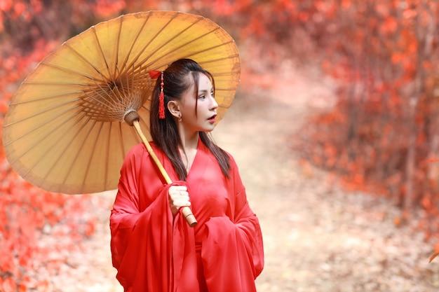 Schöne asiatische frau im roten chinesischen kostüm mit altem regenschirm im roten baum der natur mit ruhigem