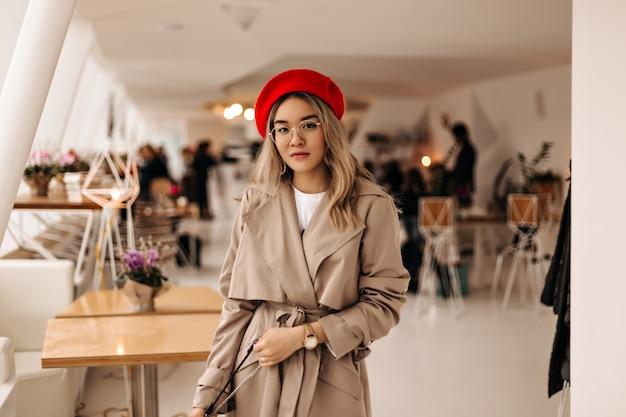 Schöne asiatische frau im trendigen trenchcoat und in der hellen baskenmütze hält tasche und schaut nach vorne gegen gemütliches zimmer
