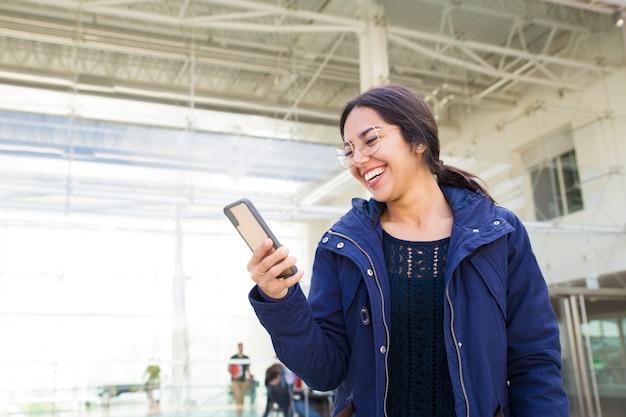 Schöne asiatische frau in den brillen, die smartphone betrachten