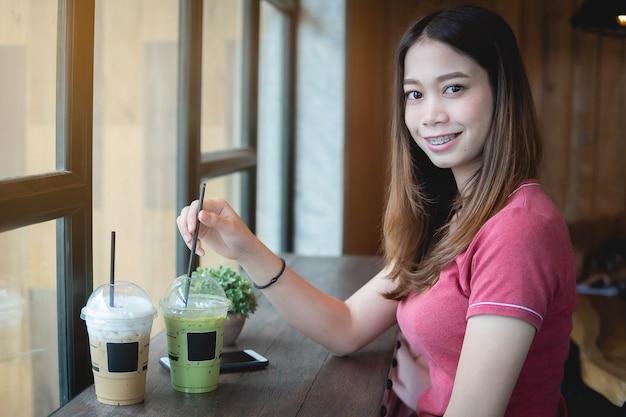 Schöne asiatische frau in der kaffeestube, kamera betrachtend, mit gefrorenem cappuccino und matcha grünem tee