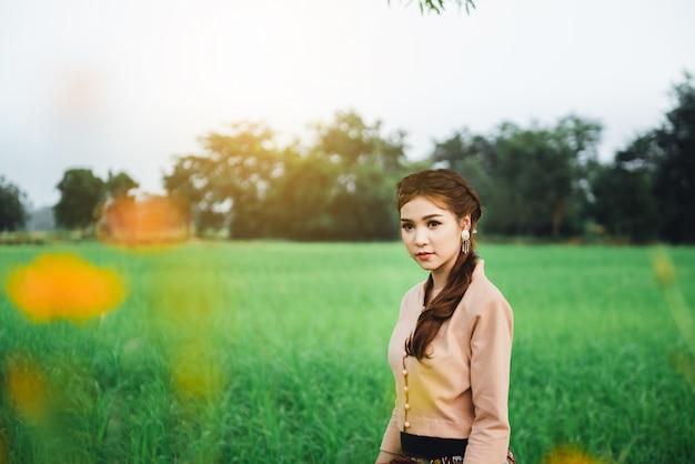 Schöne asiatische frau in der lokalen kleiderstellung und genießen natürlich auf bambusbrücke auf dem reisgebiet