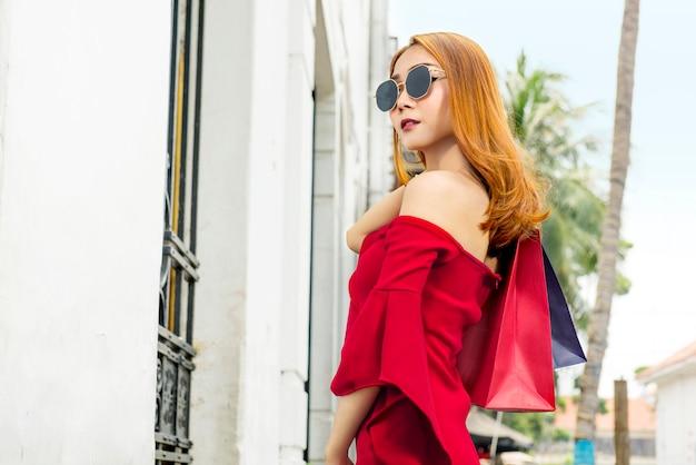 Schöne asiatische frau in der sonnenbrille, die einkaufstaschen hält