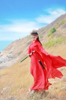 Schöne asiatische frau in voller länge im roten chinesischen kostüm mit schwarzer klinge, sie stehend auf moutain mit ruhigem