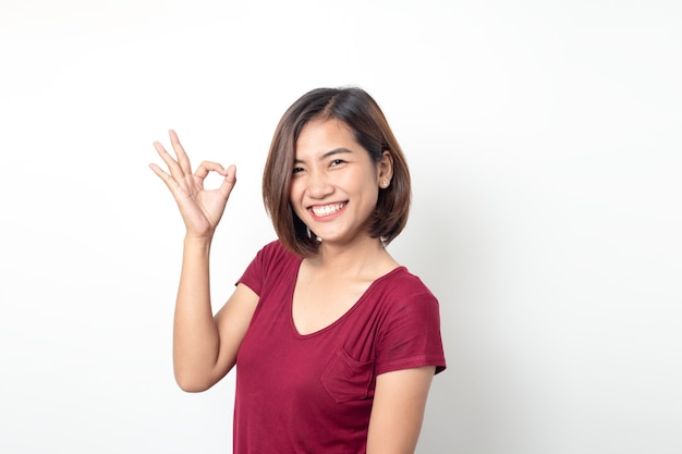 Schöne asiatische frau lächelnd mit hand ok zeichen auf einem weißen isolierten hintergrund