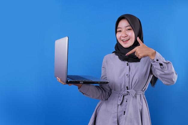 Schöne asiatische frau lächelt und zeigt ihren laptop