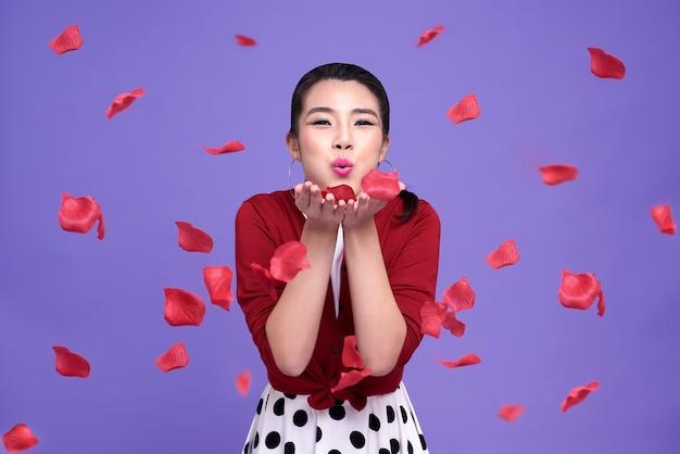 Schöne asiatische frau mit ausdrucksglück am valentinstag. mädchen bläst rosenblätter von ihren händen auf lila.