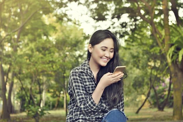 Schöne asiatische frau mit dem entspannenden telefon