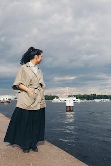Schöne asiatische frau mit dem haar in der japanischen art und im kimono gehend auf die ufergegend