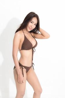 Schöne asiatische frau mit dem langen braunen haar, das braunes bikinikleid in einer sommermode trägt, die studioschuss lokalisiert auf weißem hintergrund und schatten aufwirft.