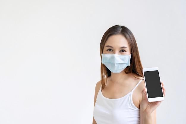 Schöne asiatische frau mit der medizinischen gesichtsmaske, die smartphone für kopienraum auf weißem hintergrund hält.