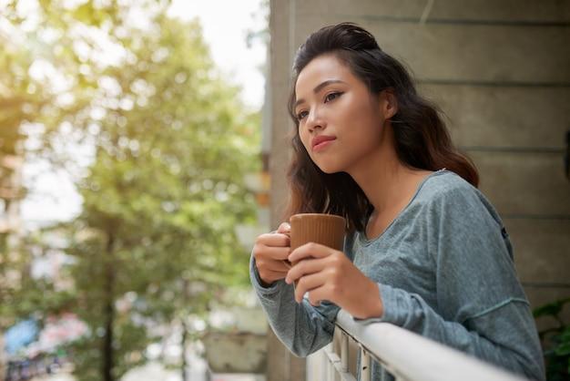 Schöne asiatische frau mit der tasse tee schauend aus ihrem balkon heraus