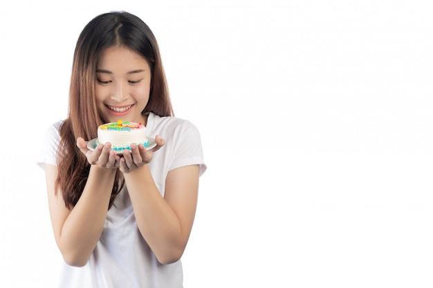 Schöne asiatische frau mit einem glücklichen lächeln, das in der hand einen kuchen hält
