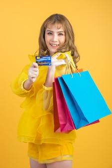 Schöne asiatische frau mit einkaufstasche und kreditkarte in der hand