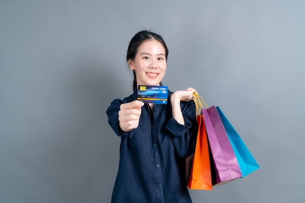 Schöne asiatische frau mit einkaufstaschen und kreditkarte lokalisiert auf grauer wand