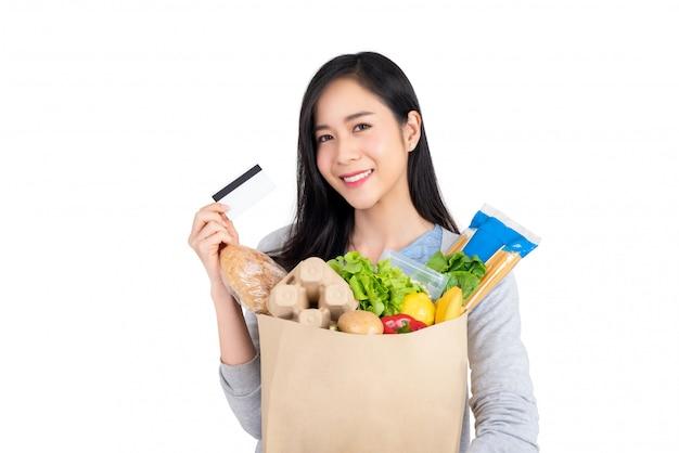 Schöne asiatische frau mit kreditkarte, die papiertüte voll von lebensmitteln lokalisiert auf studio weißem hintergrund hält