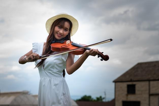 Schöne asiatische frau mit langen haaren spielt eine geige
