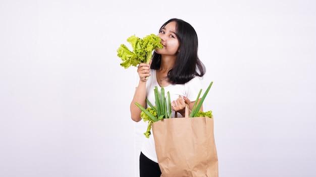 Schöne asiatische frau mit papiertüte des frischen gemüses und des haltensalats mit der isolierten weißen oberfläche