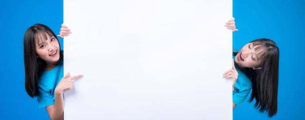 Schöne asiatische frau mit ponyfrisur im blauen t-shirt lächelt und zeigt mit dem finger eine leerstelle für werbebanner, leere kopienraum weiße tafel ein leeres banner einzeln auf blauem hintergrund