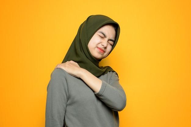 Schöne asiatische frau mit schulterschmerzen