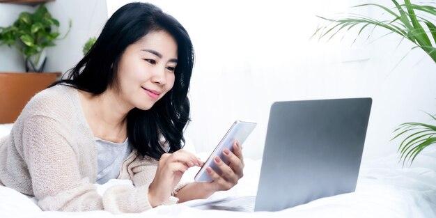 Schöne asiatische frau mit smartphone und laptop im bett liegend, frau mit technologie-internet verbunden