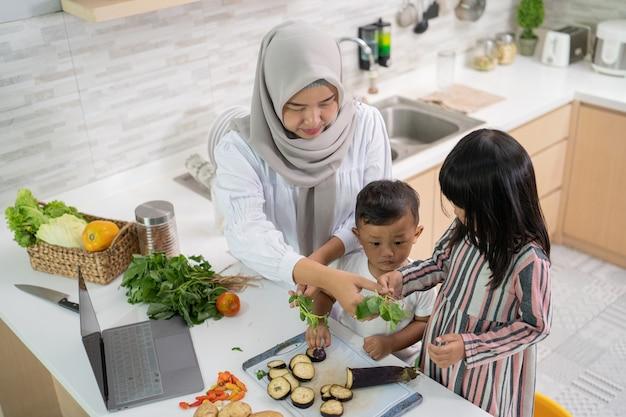 Schöne asiatische frau mit tochter und sohn, die abendessen während des ramadan für iftar kochen, der das fasten bricht