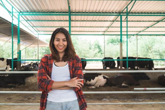 Schöne asiatische frau oder landwirt mit und kühe im kuhstall auf der molkerei, die landwirtschaft bewirtschaftet
