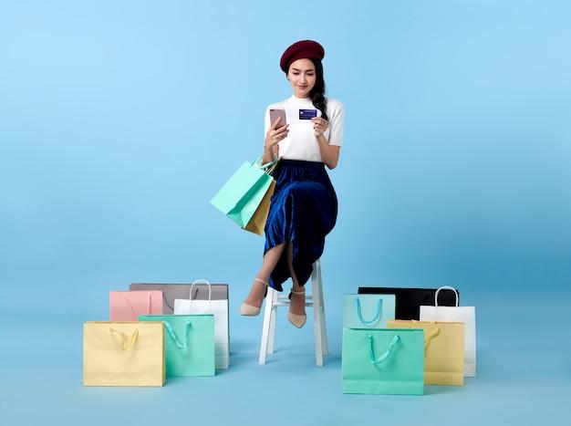 Schöne asiatische frau shopper sitzen und einkaufstaschen mit verwendung von kreditkarte und handy in den händen auf blauem raum.