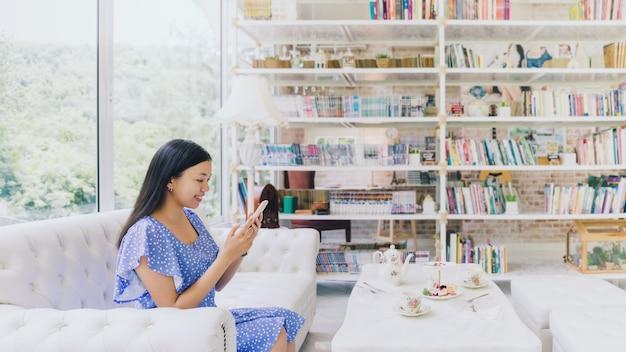 Schöne asiatische frau sitzt und verwendet smartphone zu hause, das tee trinkt