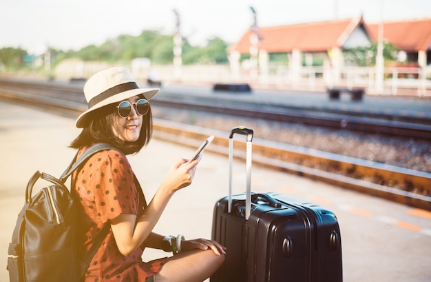 Schöne asiatische frau touristin mit handy und wartezug am bahnhof, reise- und urlaubskonzept