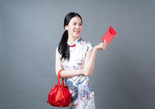 Schöne asiatische frau trägt chinesisches traditionelles kleid mit rotem umschlag oder rotem paket auf grauem hintergrund