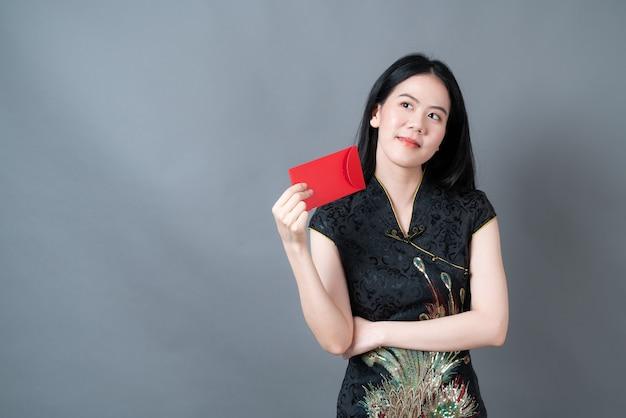 Schöne asiatische frau trägt traditionelle chinesische kleidung mit rotem umschlag oder rotem paket auf grauem hintergrund
