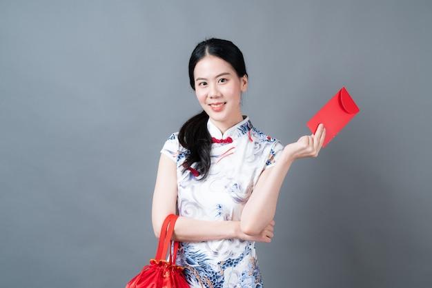 Schöne asiatische frau tragen chinesisches traditionelles kleid mit rotem umschlag auf grauer oberfläche