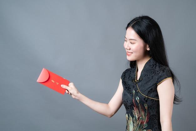 Schöne asiatische frau tragen chinesisches traditionelles kleid mit rotem umschlag oder rotem päckchen