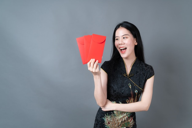 Schöne asiatische frau tragen chinesisches traditionelles kleid mit roten umschlägen auf grauer oberfläche