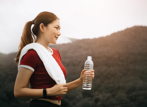 Schöne asiatische frau trainiert draußen und trinkt wasser