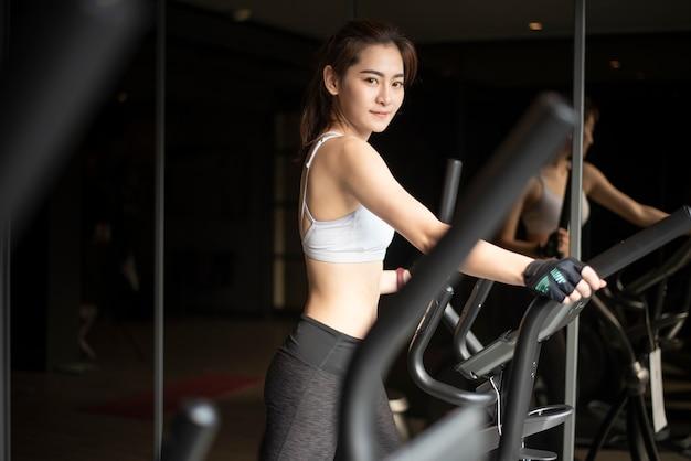 Schöne asiatische frau tut übung in der turnhalle