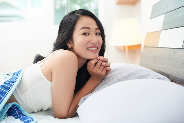 Schöne asiatische frau unter decke im bett