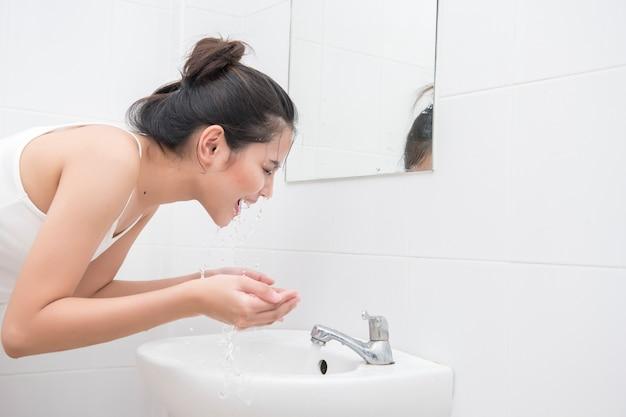 Schöne asiatische frau wäscht ihr gesicht