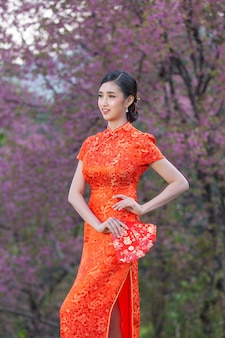 Schöne asiatische frau zeigt etwas und nimmt rote umschläge im chinesischen neujahr