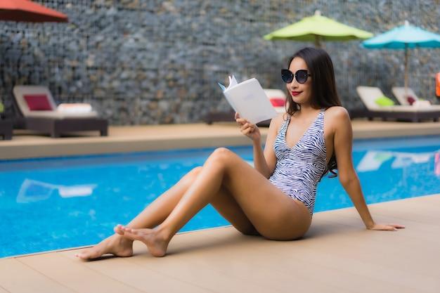 Schöne asiatische frauen des porträts lasen buch um swimmingpool im freien