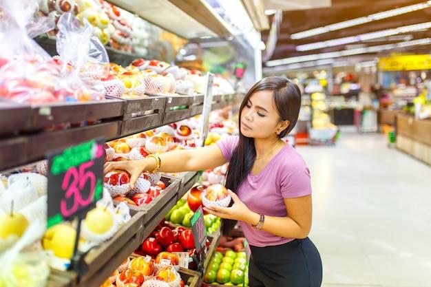 Schöne asiatische frauen, die gemüse und früchte im supermarkt kaufen