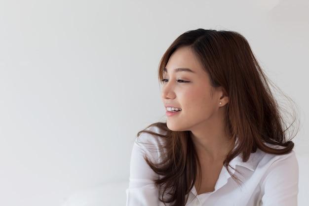 Schöne asiatische frauen, die im urlaub im bett lächeln.